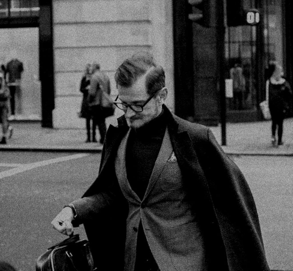 A black and white photograph of a man in a suit walking down the street