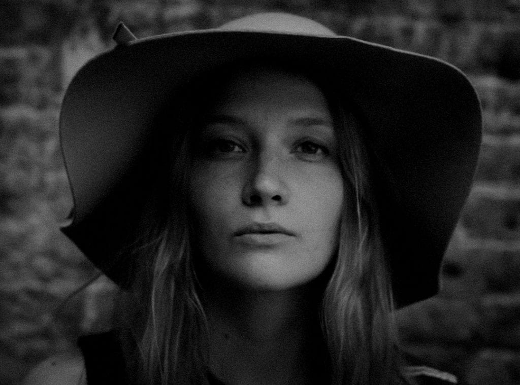 A black and white photography of a woman wearing a floppy hat, looking back at the camera