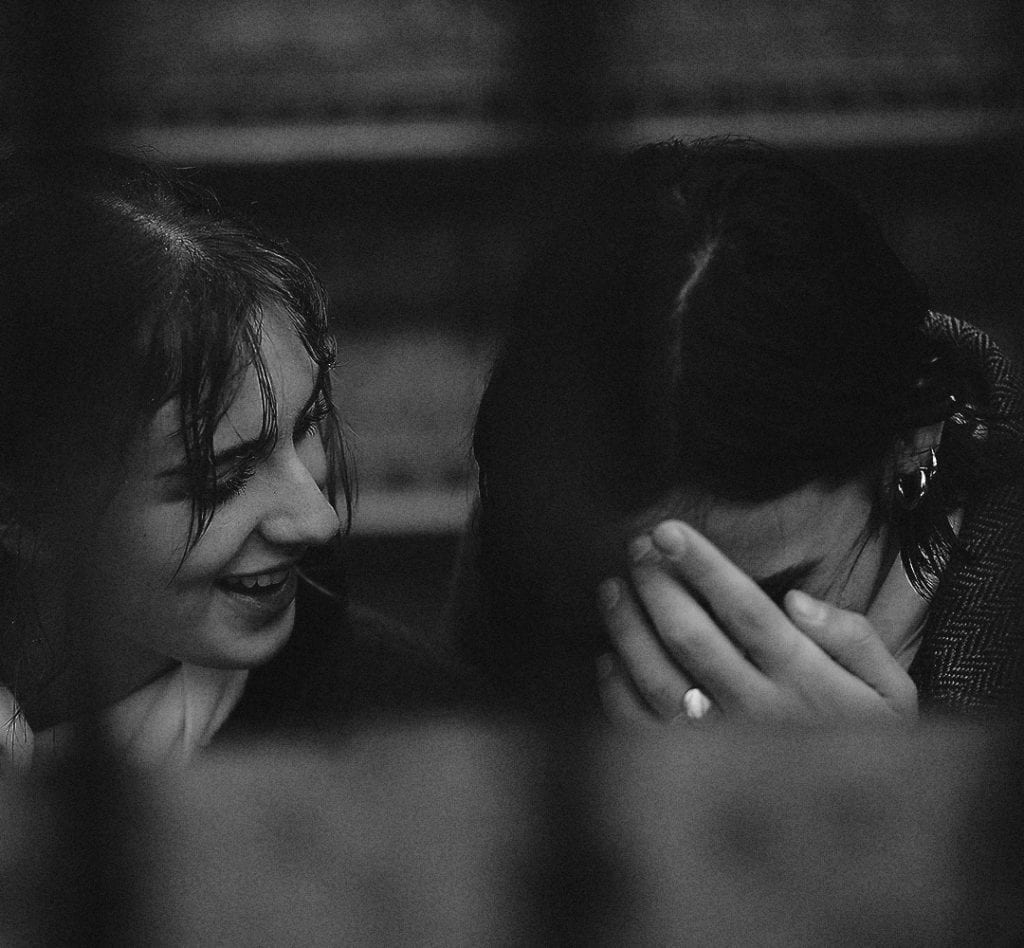 A black and white photograph of a couple smiling at each other