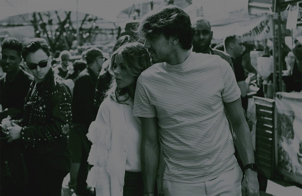 A black and white photograph of a couple holding hands as they walk through a market