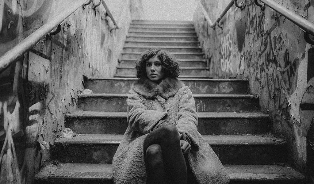 A black and white photograph of a woman sitting on subway steps