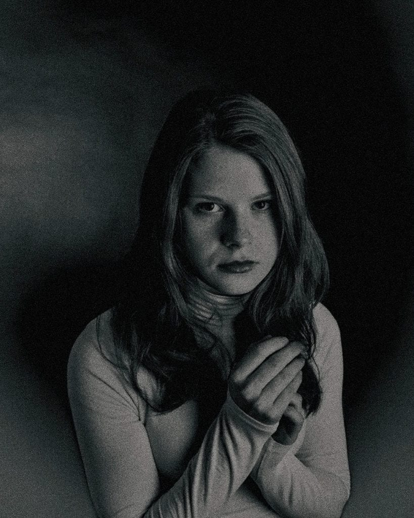 A black and white photograph of a woman in a studio looking at the camera
