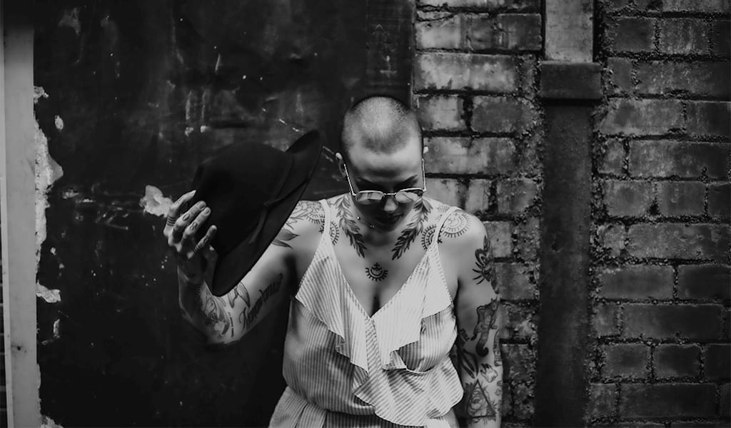 A black and white photograph of a woman with tattoos, holding a hat