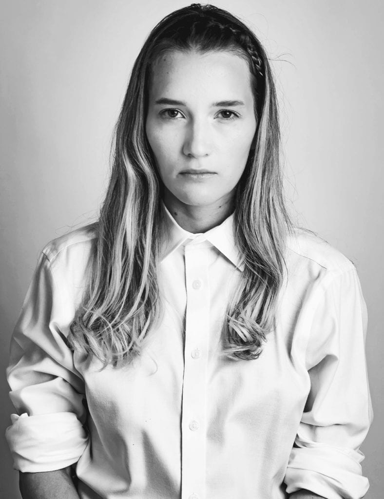 A black and white photograph of a woman wearing a white shirt and with her hair over her shoulders
