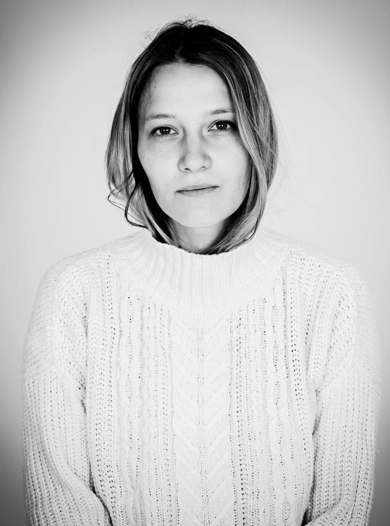 A black and white photograph of a woman wearing a white jumper and with her hair tucked into it
