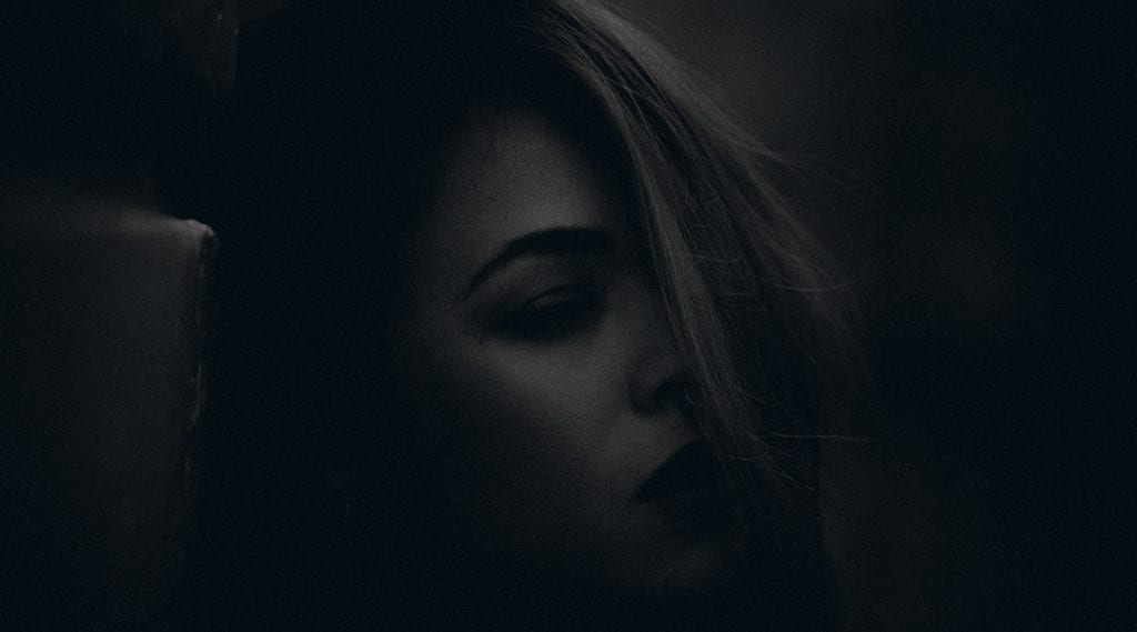 A very dark black and white photograph of a woman with her hair across her face