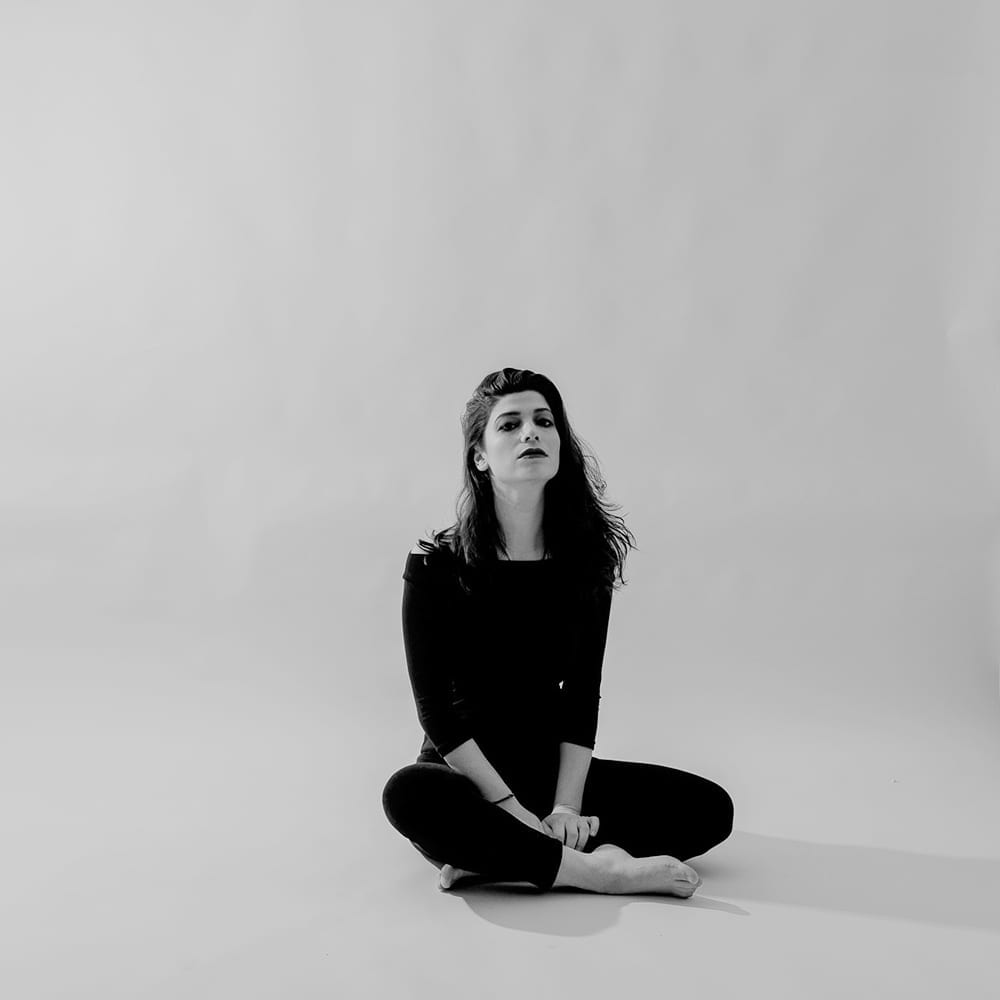 A black and white photograph of a woman sitting cross legged as she sits in a studio space