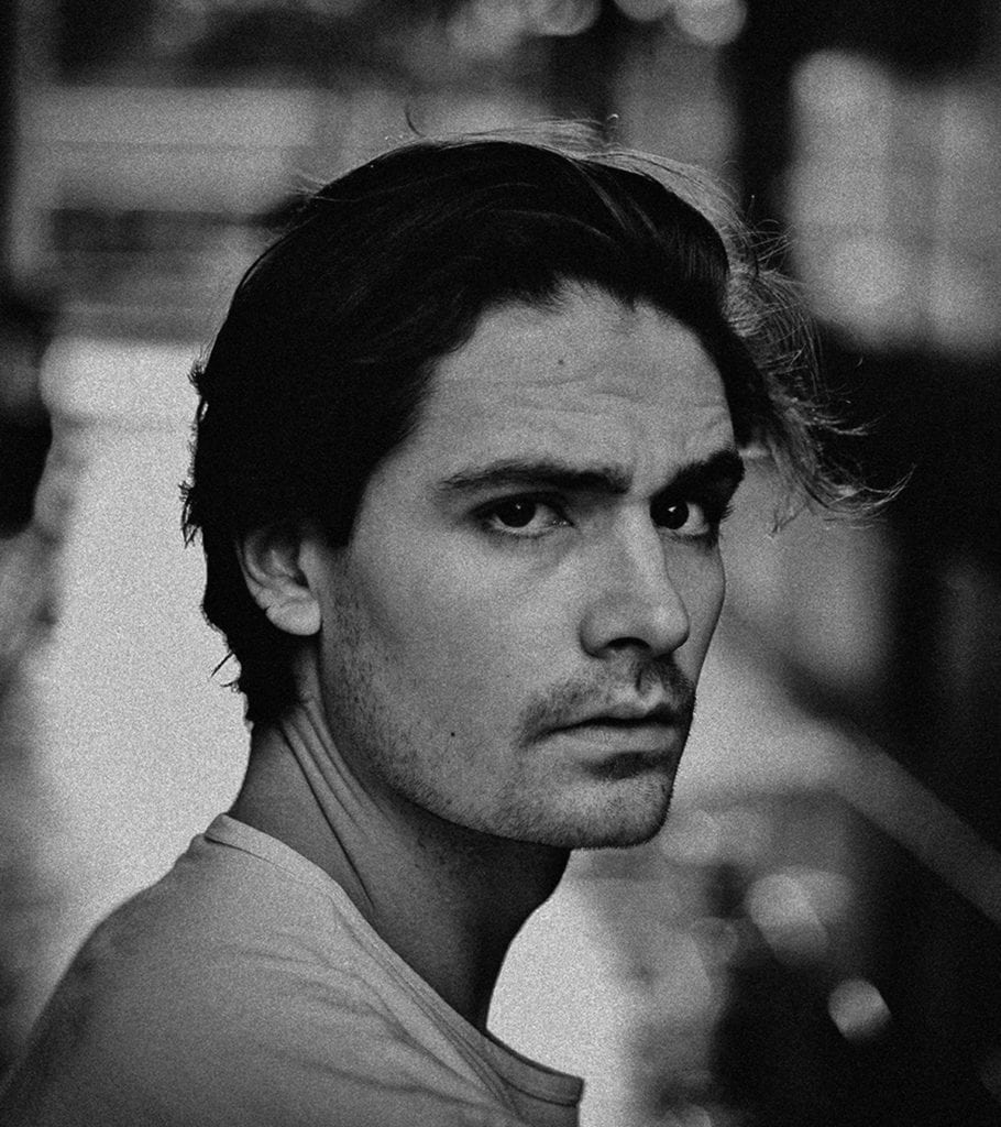 A black and white photograph of a man in a white t-shirt looking towards the camera