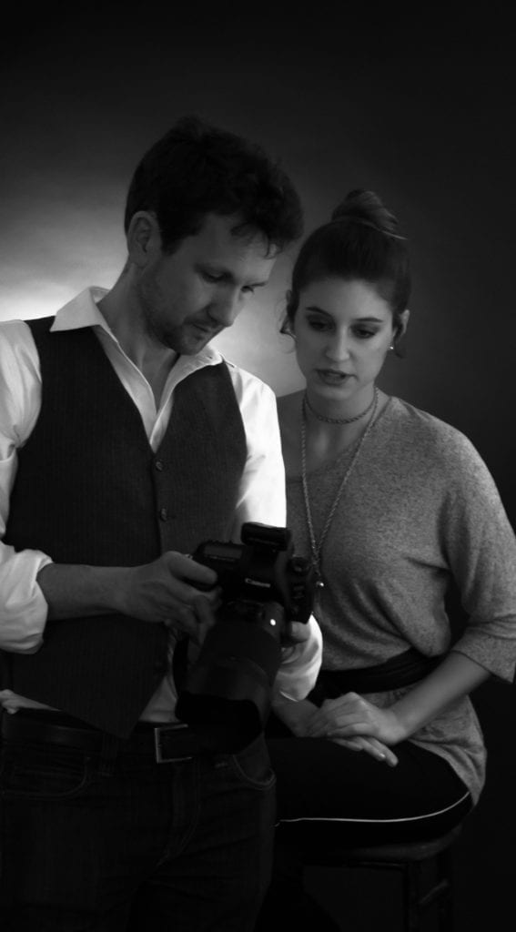 A black and white photograph of a man showing a woman the back of a camera