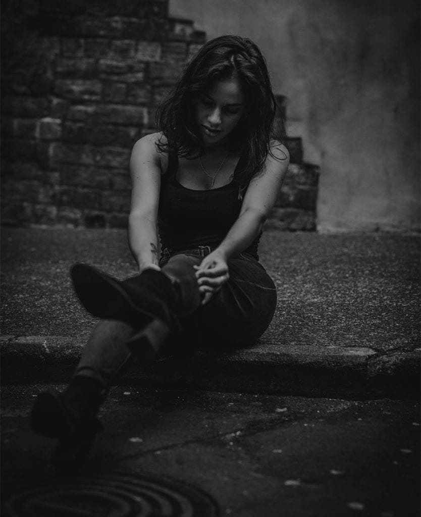 A black and white image of a woman sat on the pavement