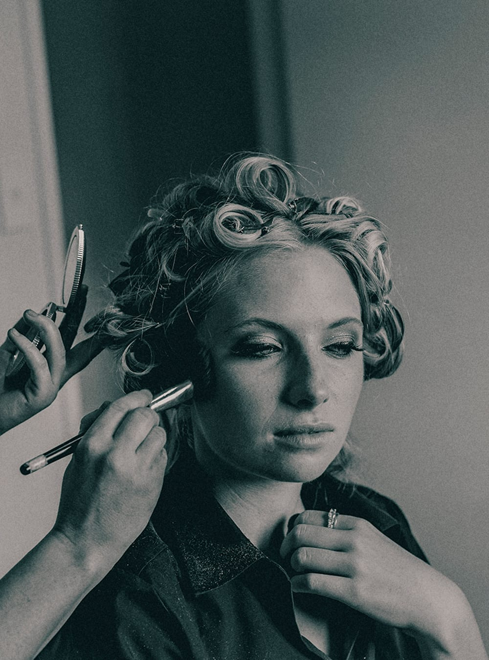 A black and white photograph of a woman having make up applied to her cheek