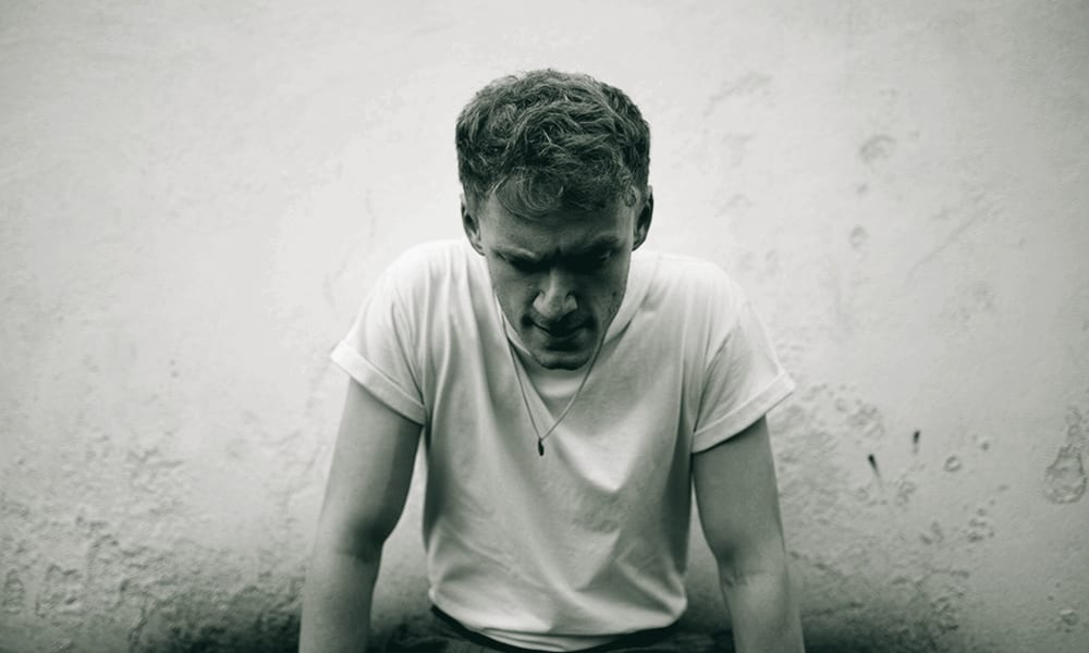 A black and white photograph of a man in a white t-shirt looking down at the ground