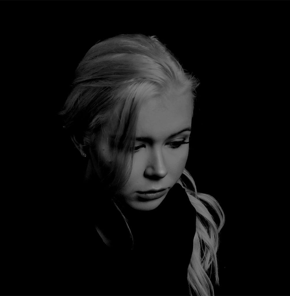 A black and white photograph of a woman with blonde hair, resting her chin on her hand