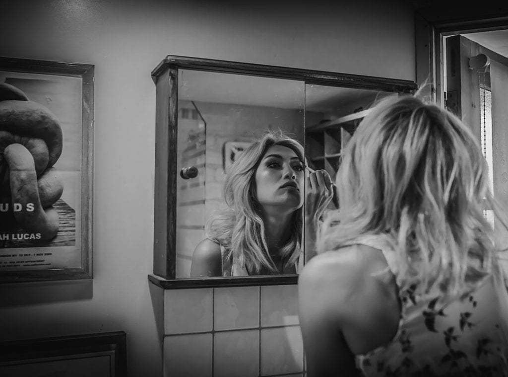 a woman adjusts her make up as she looks at a mirror