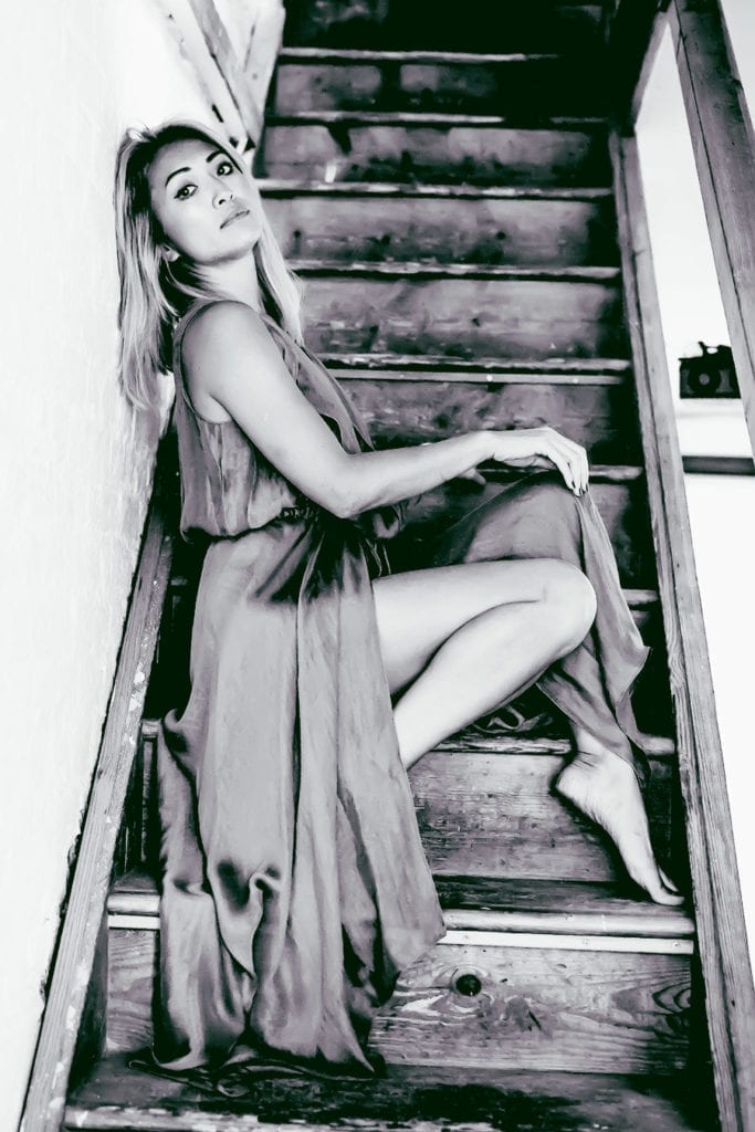 a woman sits on a staircase with her back to the wall
