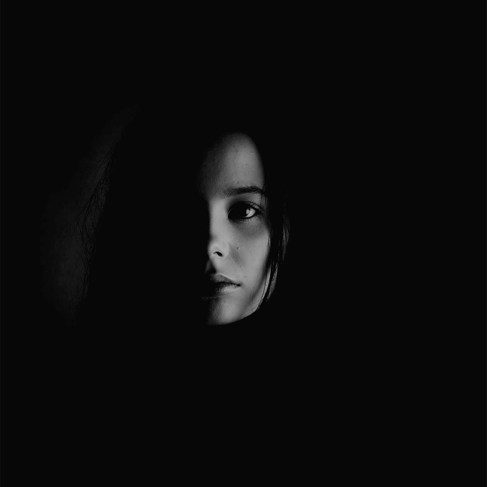 A dark black and white photograph of a woman with half her face in darkness