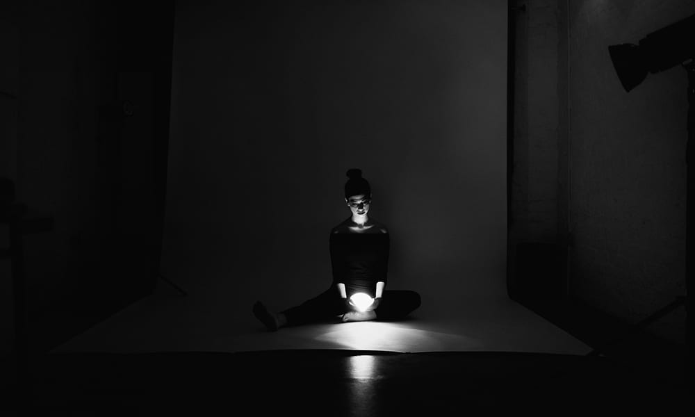 A black and white photograph of a woman sitting in darkness holding a light