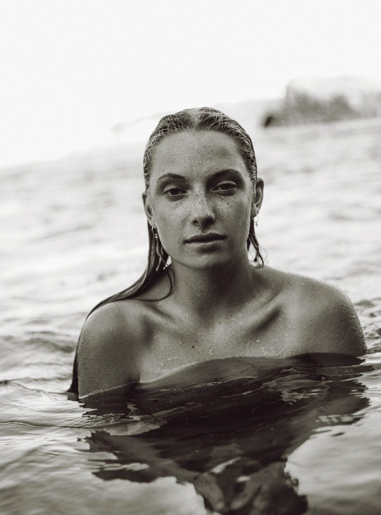 a black and white photo of a woman sitting in the sea
