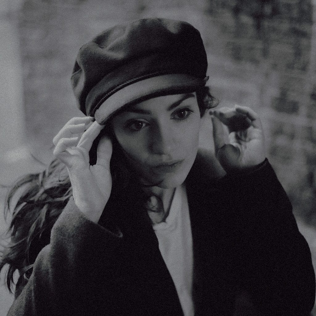 A black and white photo of a woman touching the brim of a hat