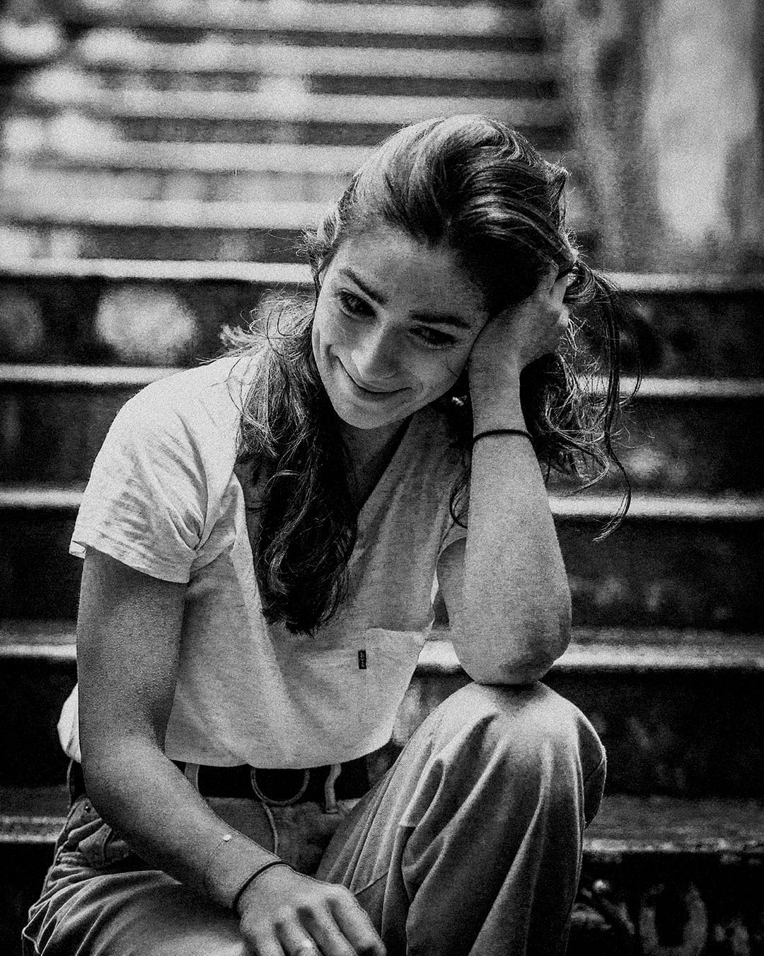 A black and white photo of a woman sitting on a step smiling
