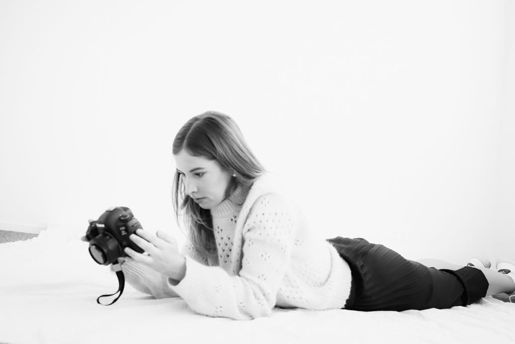 a woman lying on the floor looks at the back of a camera