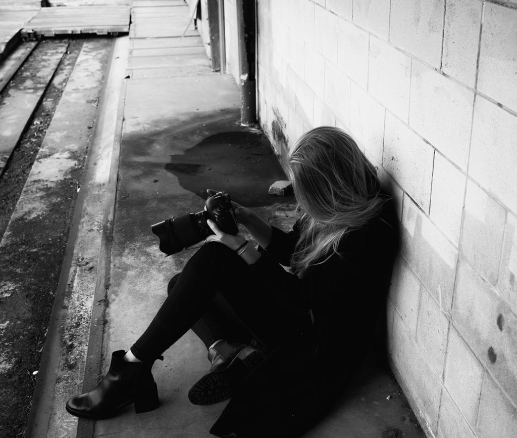 a woman with blonde hair sitting on the ground looks at the back of a camera