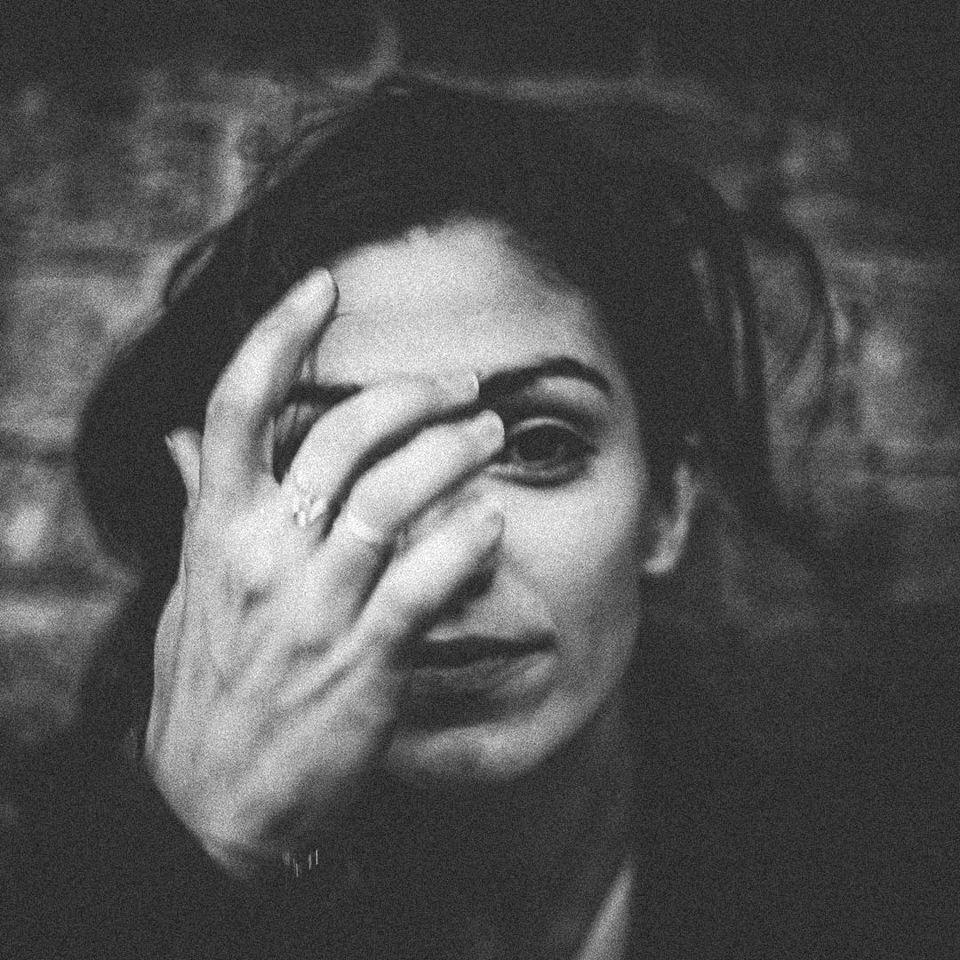 A black and white photo of a woman raising her hand to her face