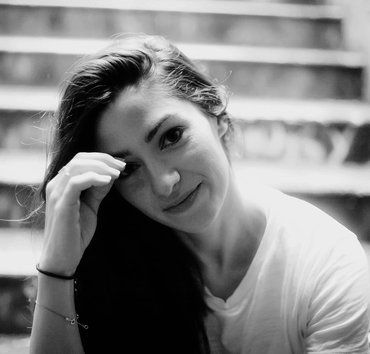 A woman in a white t shirt and with dark hair sits on steps and looks at the camera