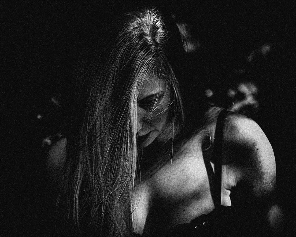 a black and white photo of a woman with blonde hair looking down