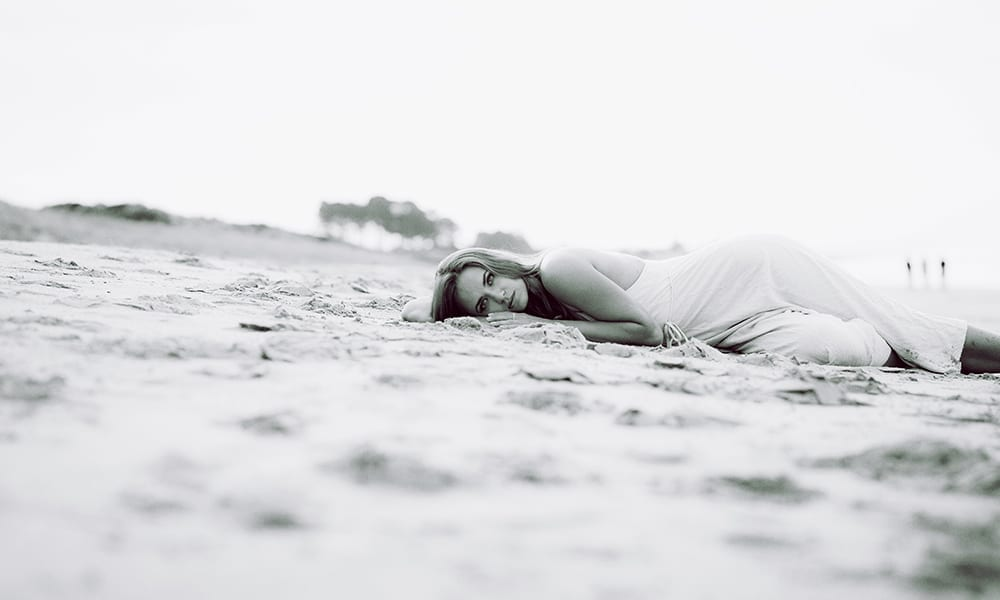 a woman lies on the sand looking at the camera