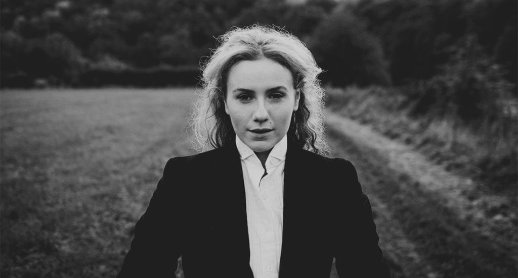 A black and white photo of a woman with blonde hair standing in a field