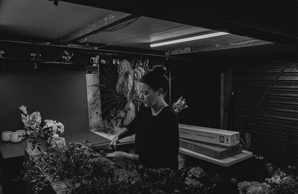 a woman cuts flowers as she works on a flower bouquet
