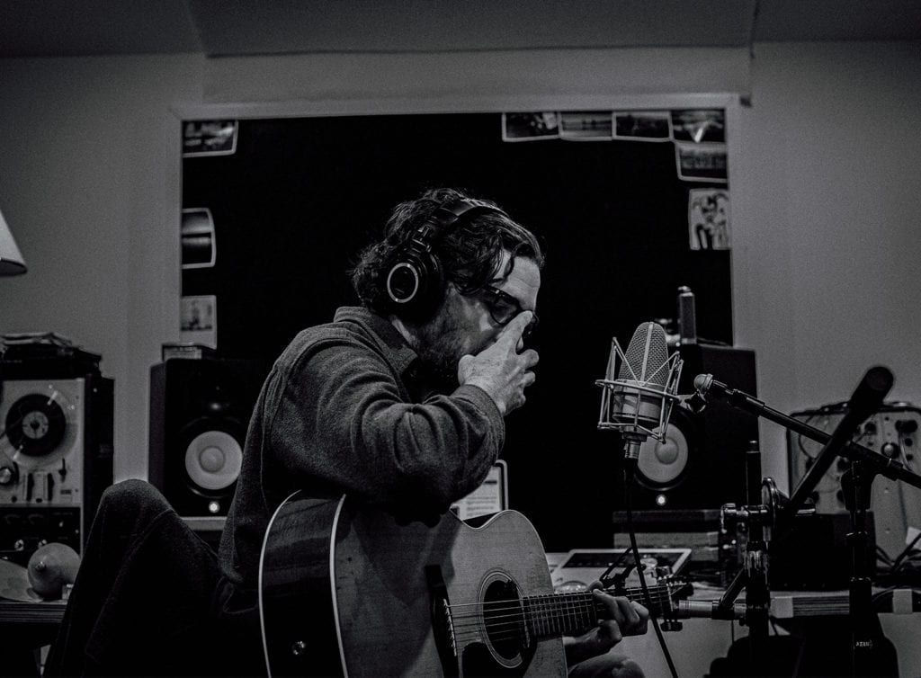 a man touches his glasses as he prepares to sing into a microphone in a music studio