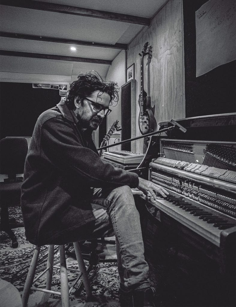 A black and white photo of a man wearing glasses sitting at a piano