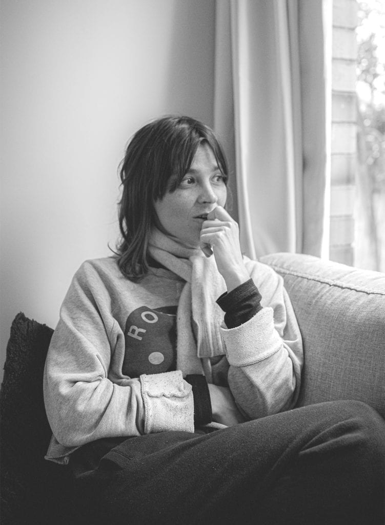 A black and white photo of a woman sitting on a sofa