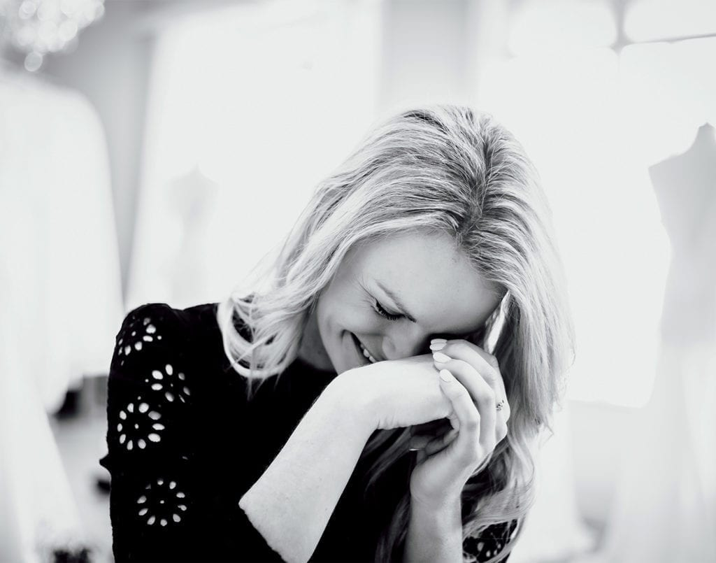 A black and white photo of a woman with blonde hair smiling as she bows her head