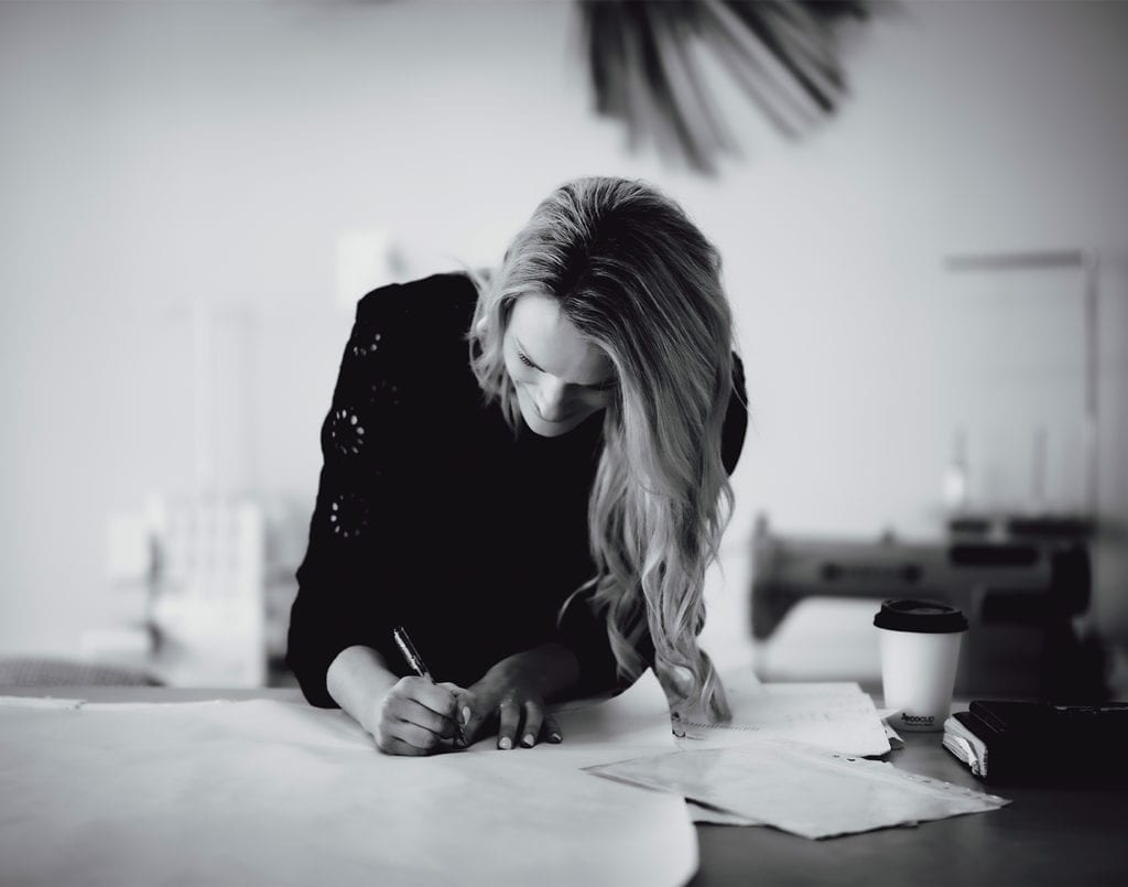 A black and white photo of a woman standing at a table drawing a gown with a pencil