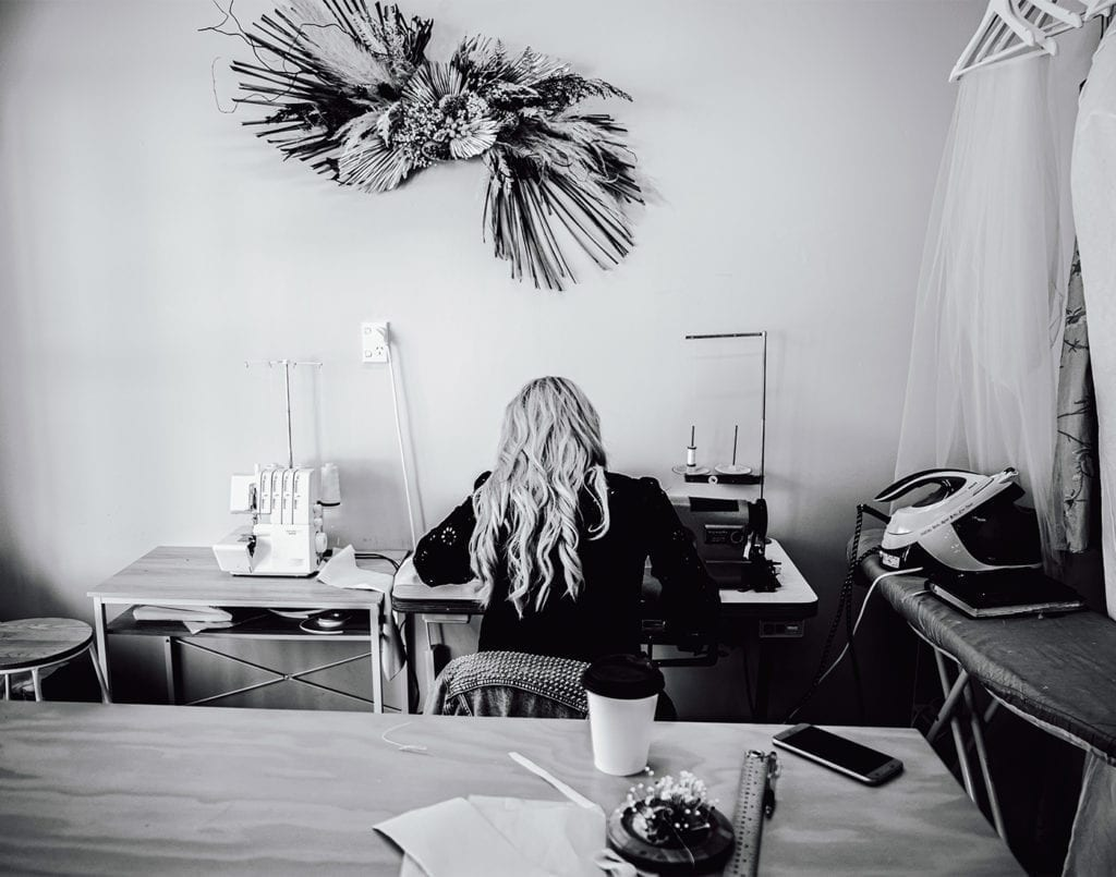 A black and white picture of a woman sitting at a sewing table