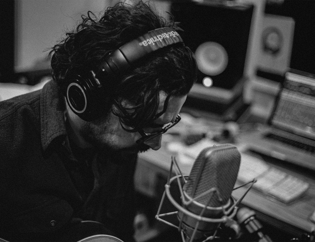 A black and white photo of a man preparing to sing into a microphone in a music studio
