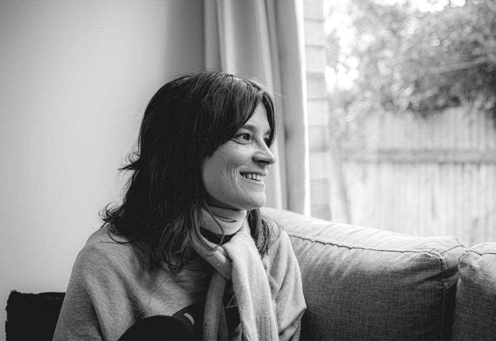 A black and white photo of a woman smiling as she sits on a sofa