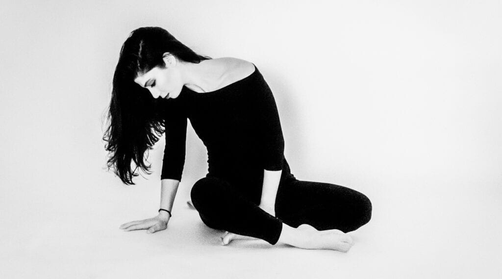 a woman wearing black sits on the floor looking down
