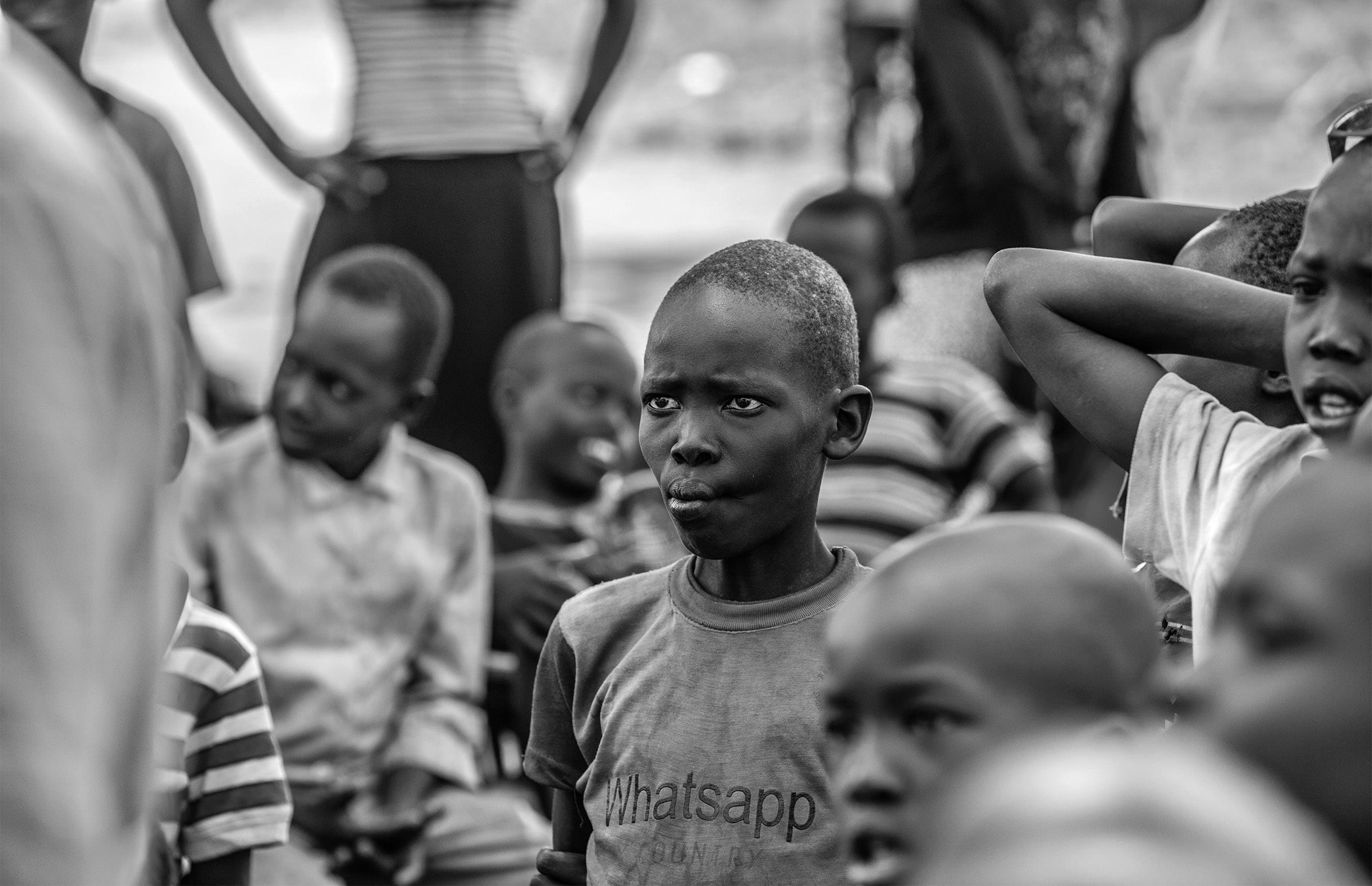 a boy stands in a crowd of children, staring and listening to someone speak
