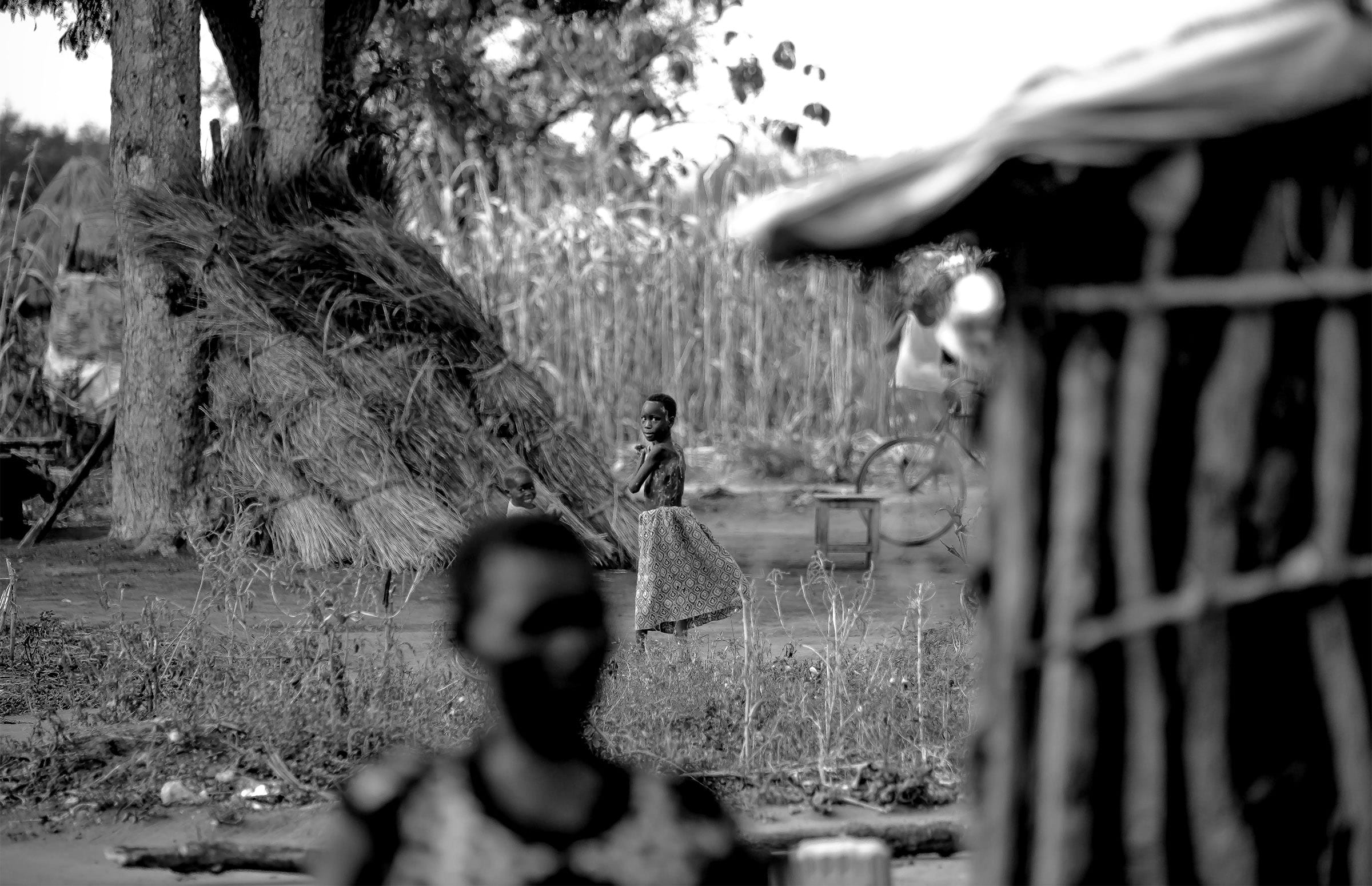 a setting of a refugee camp, with a child turning in the distance to face the camera