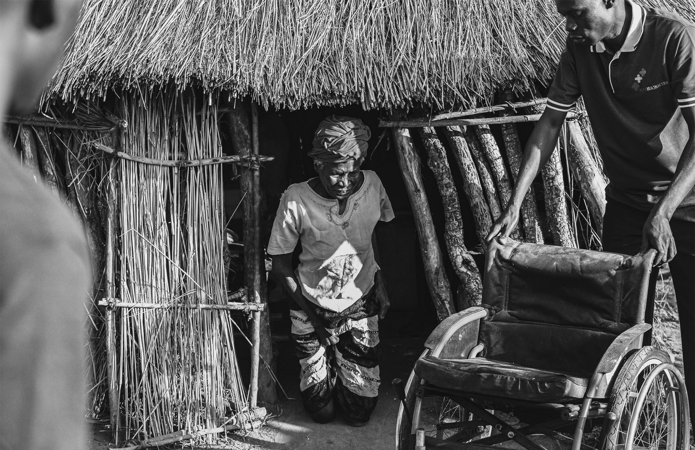 an elderly woman comes out of a hut on her knees towards a wheelchair