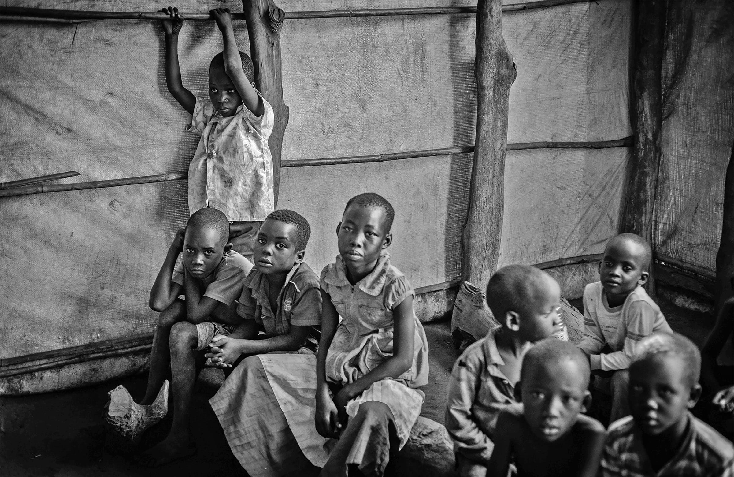 Children sitting inside a tent structure, sitting on pieces of wood