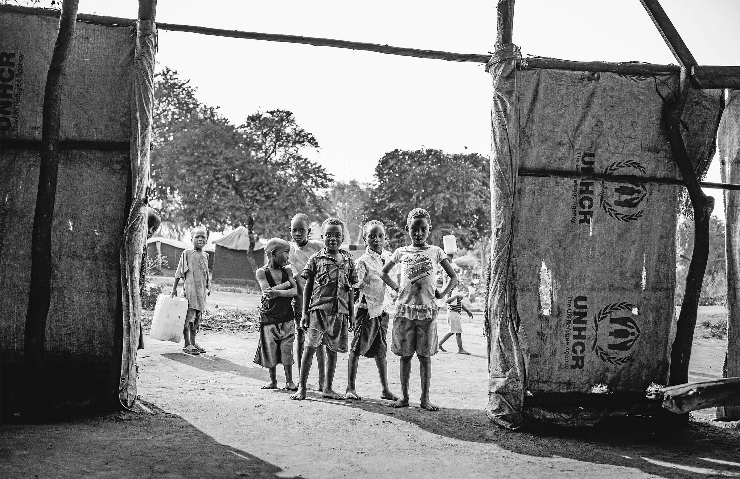 children stand in the entrance of a large tent structure, staring at the camera