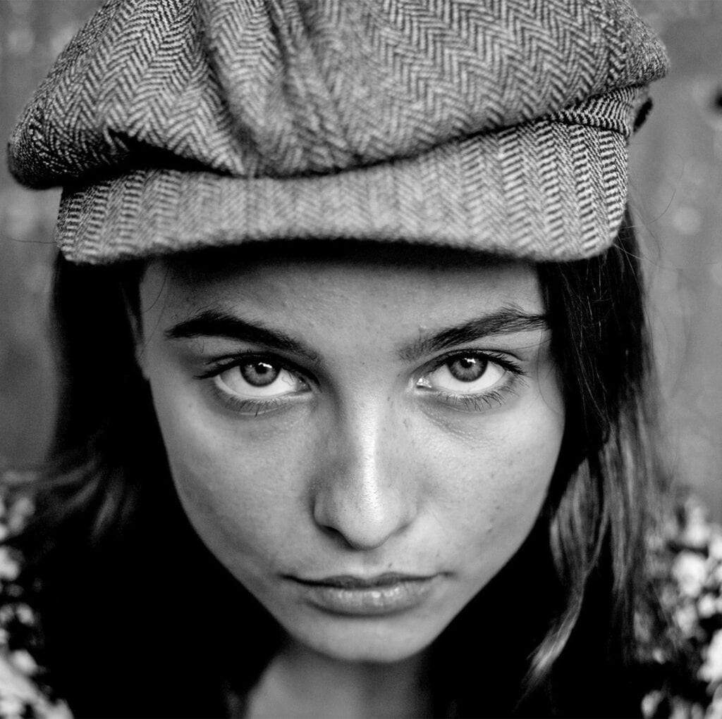 A young woman wearing a flat cap stares straight up at the camera
