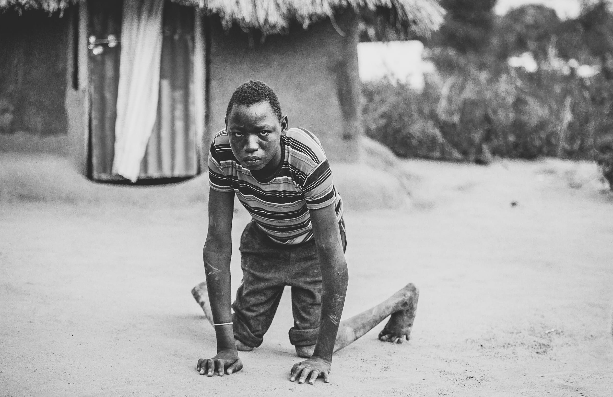 a boy looks at the camera as he sits on all fours outside a hut