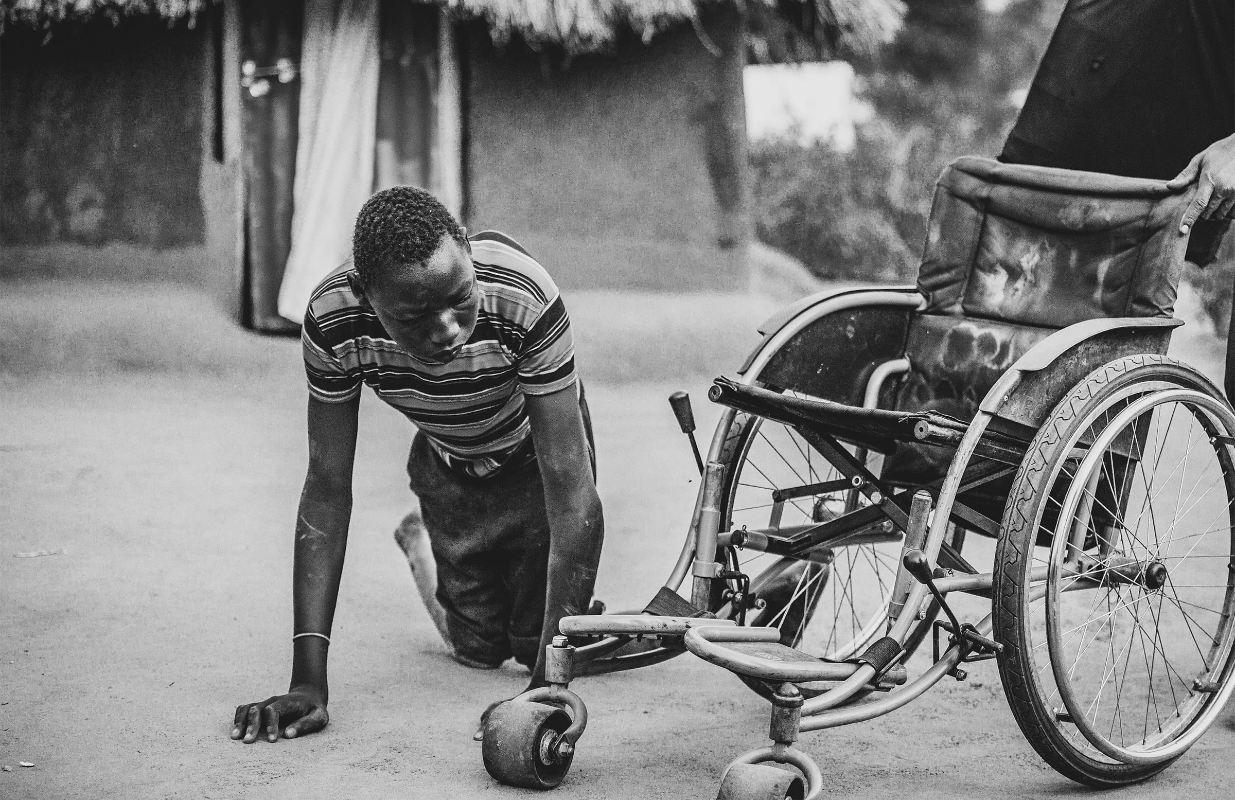 a boy prepares to get onto a wheelchair, with a hut in the background