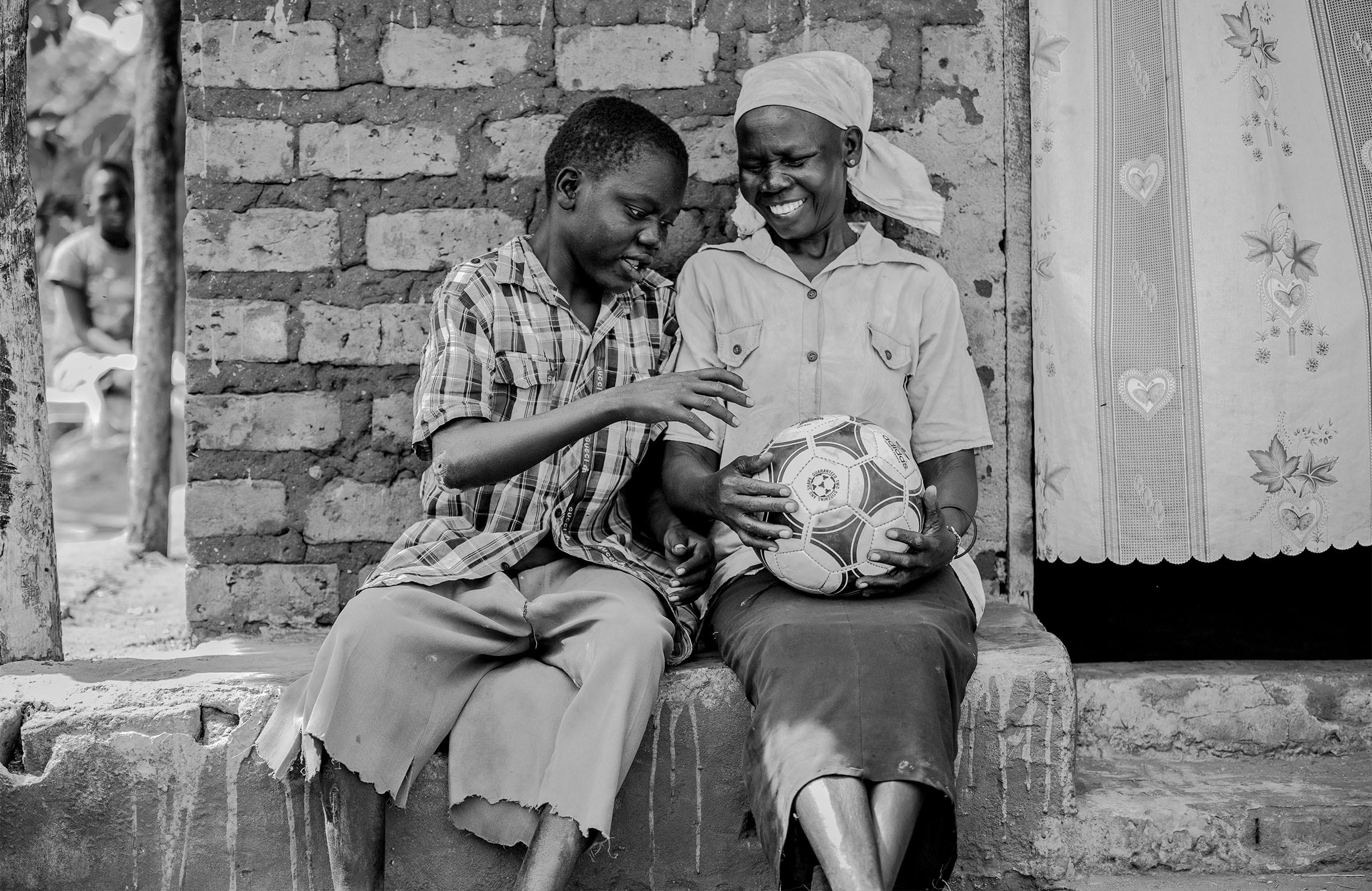 a boy sitting next to his mother reaches for a football she is holding
